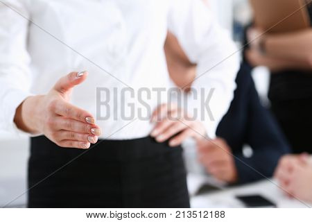 Businesswoman offer hand to shake as hello in office closeup. Serious solution friendly support service excellent prospect introduction or thanks gesture gratitude invite to participate concept