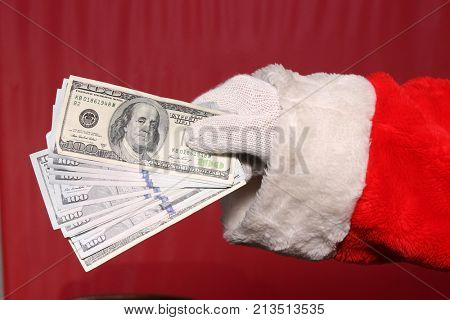 Santa Claus holds Christmas Cash. American Money in Santa's Hand.