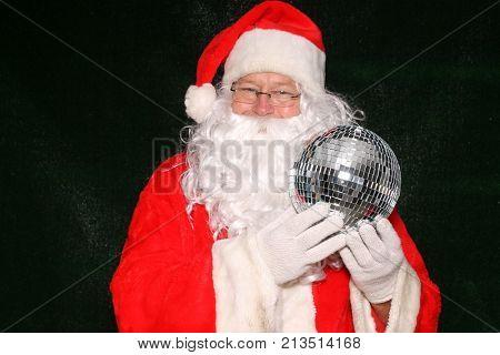Santa Claus holds a silver disco mirror ball.