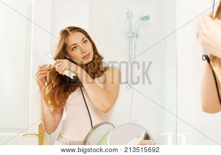 Attractive young dark-haired woman using hair straightener while looking into bathroom mirror