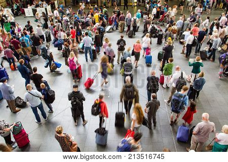 KINGS CROSS TRAIN STATION, LONDON, UK - JULY 21, 2016. An aerial view of a train station concourse packed with passengers and commuters at rush hour.