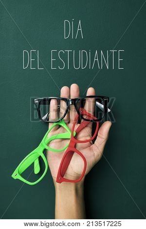 some plastic-rimmed eyeglasses of different colors in the hand of a young man and the text dia del estudiante, students day in spanish, against a green chalkboard