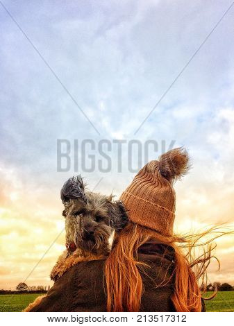 Rear view of a girl wearing a knitted hat and warm coat whilst carrying her scruffy pet dog on her shoulder.