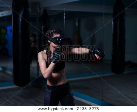 Young fighter boxer fit girl in VR glasses wearing boxing gloves in training. Boxing game in virtual reality 360 degrees. Futuristic gaming