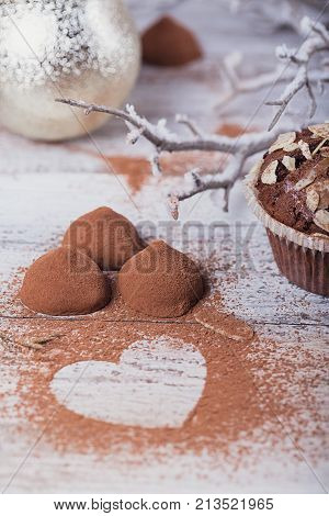 Homemade dark chocolate truffles with heart shaped cocoa powder and winter decoration on white rustic wooden table. Winter holiday background.