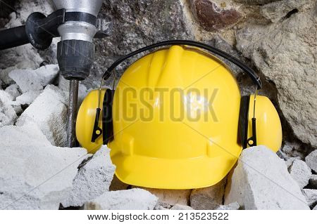 Demolition of walls. Electric hammer helmet and hearing protection lying on the rubble. Old brick and remodeled building wall. Grunt on the background of the old wall. poster