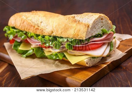 Baguette sandwich cut in half with ham,  turkey breast, cheese, lettuce and tomatoes on a cutting board closeup