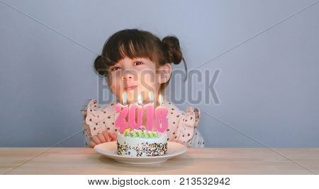 happy new year 2018. cute girl with smiley face with cake and candle number for year 2018 on the new year celebration party at home with family. seasonal and holiday background.