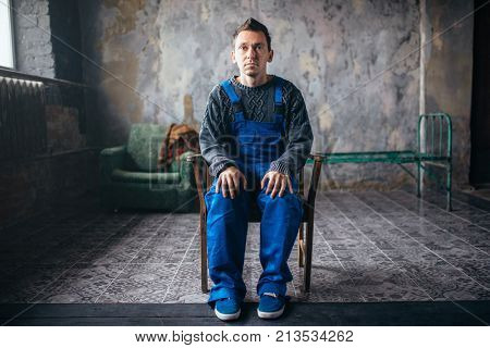 Crasy man sitting in the chair, psycho patient