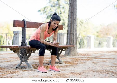 young beautiful and fit sport woman looking at mobile phone internet app tracking performance after running workout sitting on park bench happy and relaxed in healthy lifestyle concept