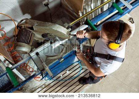 Worker In The Workshop Cuts The Pvc Profile With Circular Saw