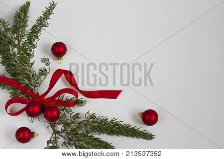 A bundle of rosemary greens tied with a red bow with Christmas ornaments on a white background.