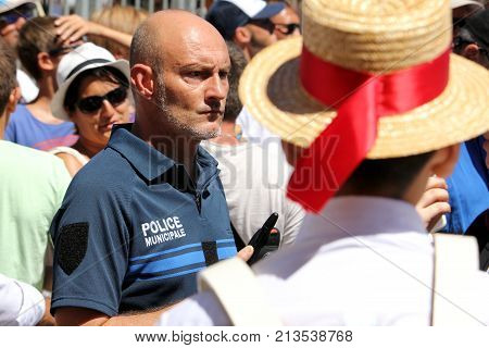 Sete, Herault, France  - Aug 21 2017: Police Municipale Officer Watches The Crowds While The Traditi