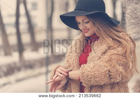 Young attractive girl outdoors in winter. She is wearing a wide-brimmed hat and a fur coat. The girl is looking at the clock