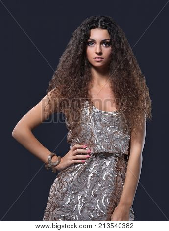 woman with long brown curly hair with healthy shine on studio background.