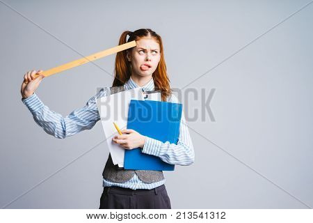 a funny young schoolgirl holding a folder with documents and a ruler, a funny face