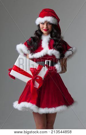 Beautiful woman in Santa Claus style dress with gift box