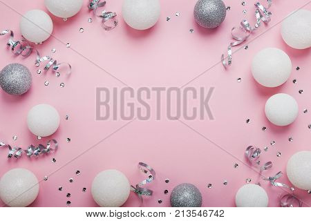 Festive frame made of christmas balls and sequins on pink table top view. Fashion background. Flat lay. Party mockup.