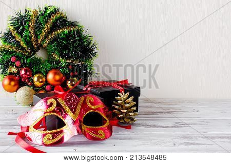 Christmas decoration wreath with red and gold ball toys and ribbon black gift box and red mask on the white wooden background. Copy space.
