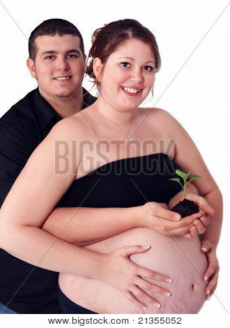 man standing behind pregnant woman holding tiny seedling. isolated