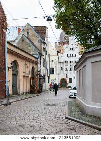 Tourists Walk To Three Brothers Houses In Riga
