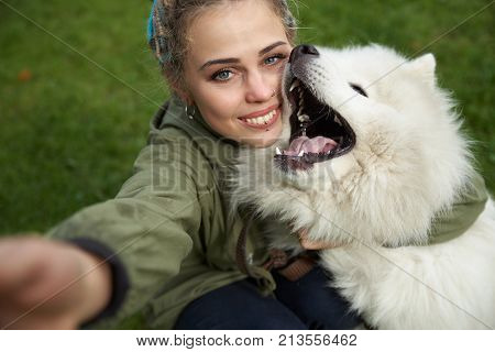 Selfie Of A Young Woman In Green Coat And Multicolored Dreadlocks With His White Samoyed Dog In The