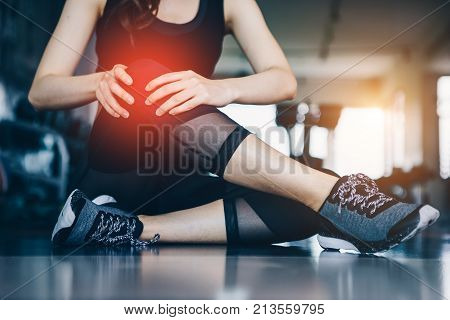 Asian woman exercising in the gym Young woman workout in fitness for her healthy and office girl lifestyle. Her knee injury from exercise.