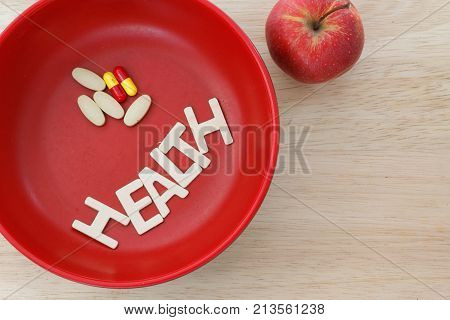 Health concept with word HEALTH and pills / capsules inside a read bowl on wooden table. Concept of health,nutrition,food,illness,disease.