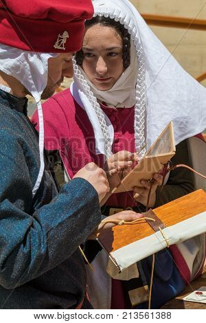 Medieval reenactors in scribe costumes practicing traditional illumination writing calligraphy with feather quill and ink, Mdina, Malta, April 2017