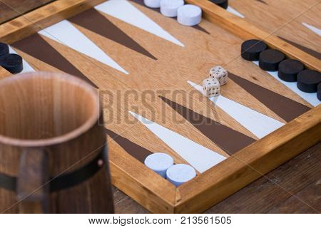 Traditional backgammon game being played in tavern handmade dice, wooden table, ale mug