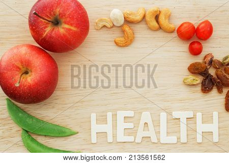 Fresh red apples green beans and cherry tomatoes on wooden chopping board with word HEALTH. Copyspace.