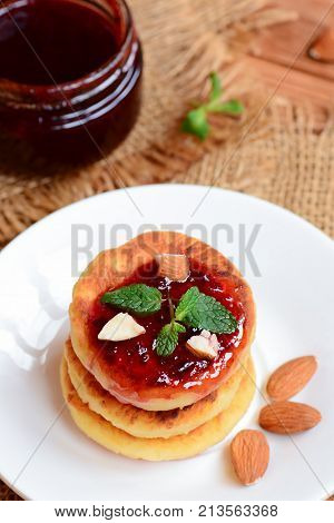 Cottage cheese cakes. Fried cottage cheese cakes with berry jam and almonds on a white plate. Traditional ukrainian syrniki recipe. Vertical photo