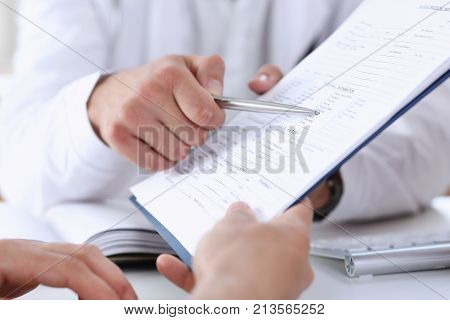 Male doctor hand hold silver pen and showing pad. Physical agreement form signature disease prevention ward round reception consent contract sign prescribe remedy healthy lifestyle concept