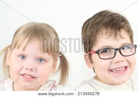 Happy little blonde girl and boy in glasses smiles in white studio