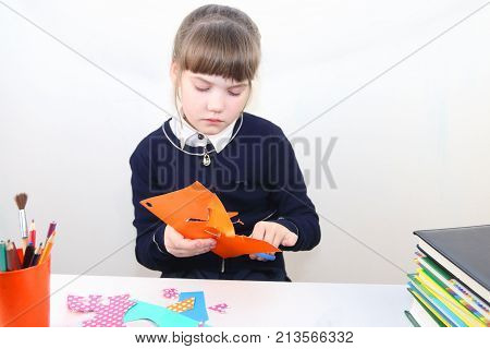School girl cuts out with scissors from colored paper on table with books in studio