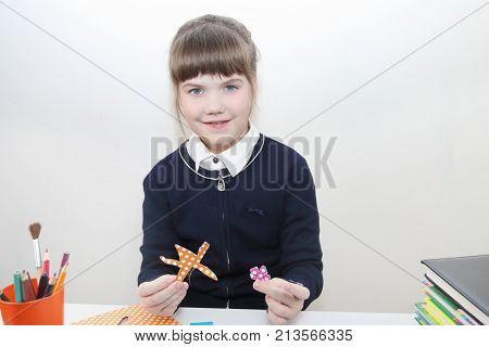 School girl shows flowers from colored paper on table with books in studio