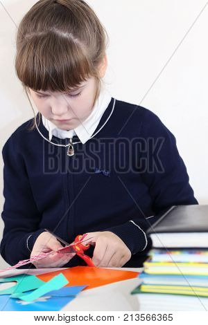 School girl cuts out with scissors from colored paper on table with books