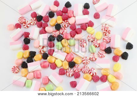 Many sweet and bright candies and marshmallows on white surface