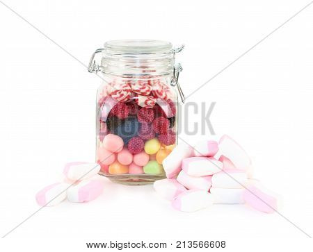 Glass jar with many bright sweet candies and marshmallows isolated on white background
