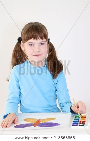Smiling pretty girl paints watercolor butterfly on table in white room