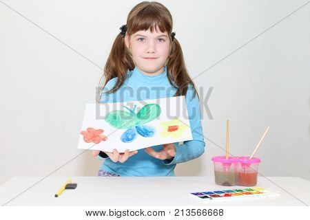 Smiling pretty girl shows picture with butterfly after watercolor painting in white room