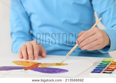 Hands of girl watercolor painting butterfly on table in room close up