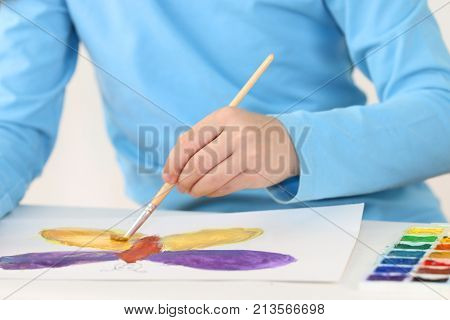 Hands of girl watercolor painting butterfly on table in white room