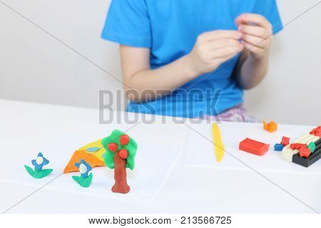 Girl hands molding house tree flowers from plasticine on table in room