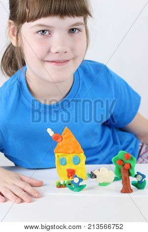 Girl sits with house tree flowers from plasticine on table in white room
