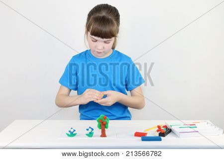Pretty girl in blue molds from plasticine on white table in white room
