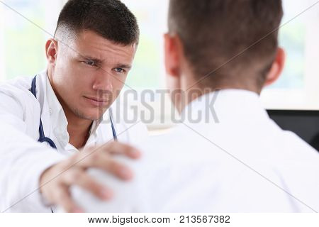 Friendly male doctor hold patient shoulder in office during reception. Examination result positive test calm down promise and cheer up grief and suffer treatment condolence ethics concept