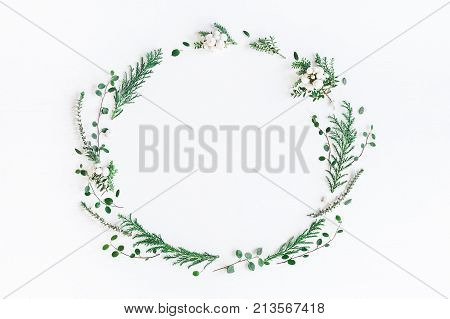 Christmas composition. Wreath made of winter plants flowers berries on white background. Christmas winter new year concept. Flat lay top view copy space