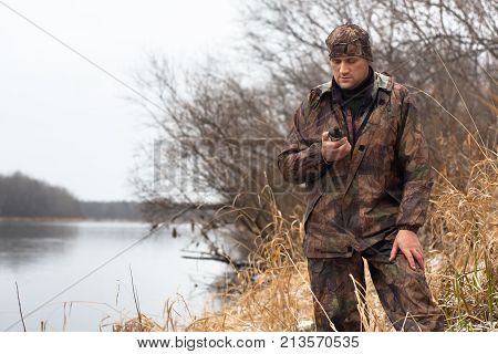 man looking on the gps navigator on the riverbank