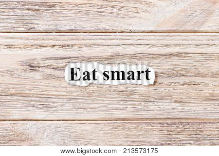 eat smart of the word on paper. concept. Words of eat smart on a wooden background.